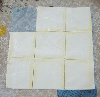 When puff pastries are slightly softened, run a knife to cut into 9 smaller squares. Apply a layer of egg wash around the sides of each square. The egg wash helps to seal the sides later.